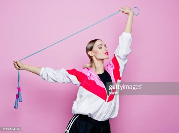 het stijlportret van de jaren '80 van zekere vrouw in sportenkleding tegen roze achtergrond - izusek stockfoto's en -beelden