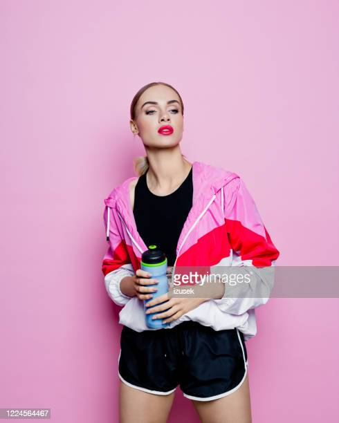 80's style portrait of excited woman in sports clothes against pink background - fashion model stock pictures, royalty-free photos & images