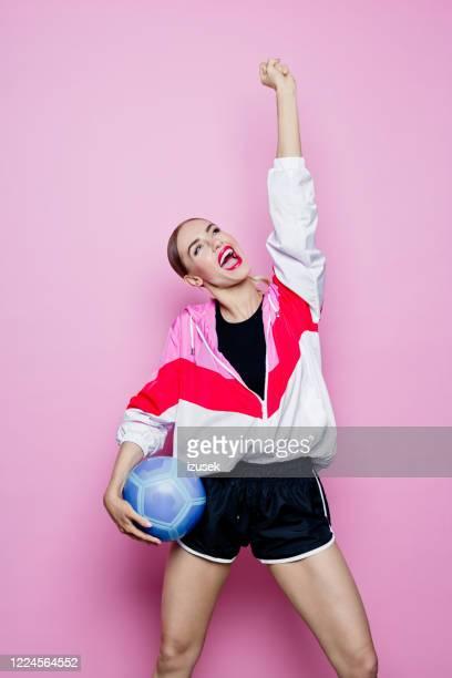 het stijlportret van de jaren '80 van opgewekte vrouw in sportenkleren tegen roze achtergrond - izusek stockfoto's en -beelden