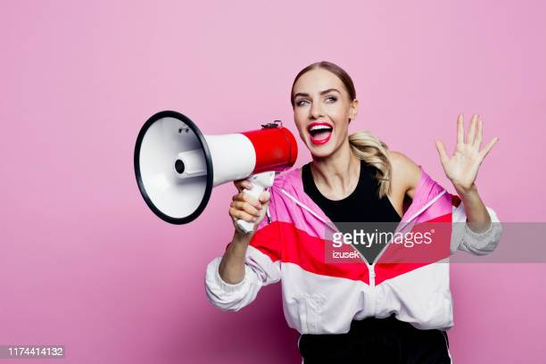 80's style portrait of happy woman in sports clothes holding megaphone - megaphone stock pictures, royalty-free photos & images