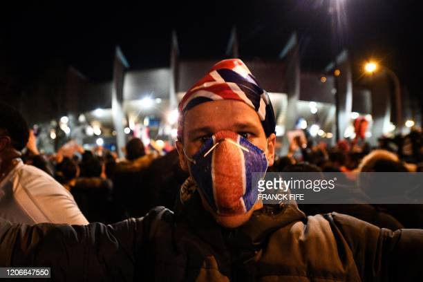 PSG's supporter celebrates outside the Parc des Princes stadium during of the UEFA Champions League round of 16 second leg football match between...