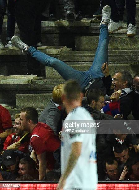 LOSC's supporters react as their tribune falls down following the goal by LOSC's Cameroonian midfielder Ibrahim Amadou during the French L1 football...