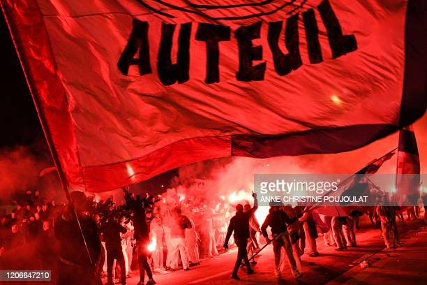 TOPSHOT PSG's supporters wave flags of the team outside the Parc des Princes stadium during of the UEFA Champions League round of 16 second leg...