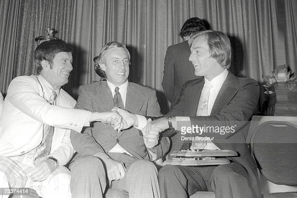 1970's Ted Lindsay shakes hands with Guy Lafleur at an award ceremony Jean Beliveau sits between them