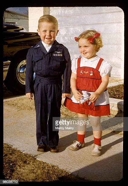 1950's toddlers happily pose in front of Dad's car