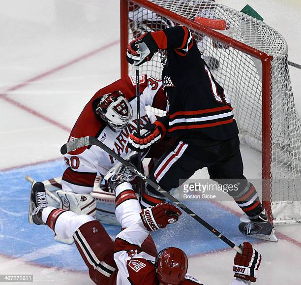 S Torin Snydeman slips the puck past Harvard goalie Raphael Girard for as second period goal that put the Huskies ahead 3-0. Harvard defenseman...