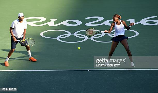 USA's Venus Williams returns the ball next to USA's Rajeev Ram as they play against USA's Jack Sock and USA's Bethanie MattekSands during their mixed...