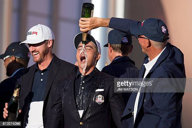 TOPSHOT USA's ViceCaptain Tom Lehman pours champagne on Rickie Fowler's head and Jimmy Walker laughs as they celebrate winning the 41st Ryder Cup at...