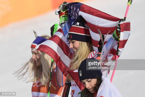 USA's winner Mikaela Shiffrin raises the US flag as she poses on the podium with Norway's second place winner Ragnhild Mowinckel and Italy's third...