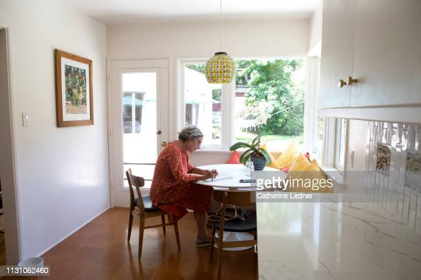 50's woman at table signing papers