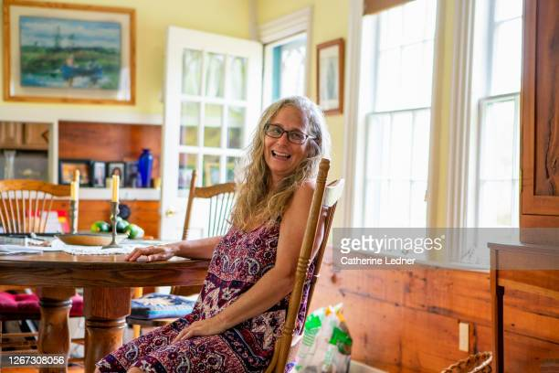 50's woman in hippie garb seated at country kitchen table looking away and laughing - catherine ledner stock pictures, royalty-free photos & images