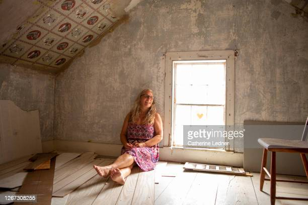 50's woman sitting alone in vintage attic that is being renovated.  she's laughing and looking away. - catherine ledner stock pictures, royalty-free photos & images