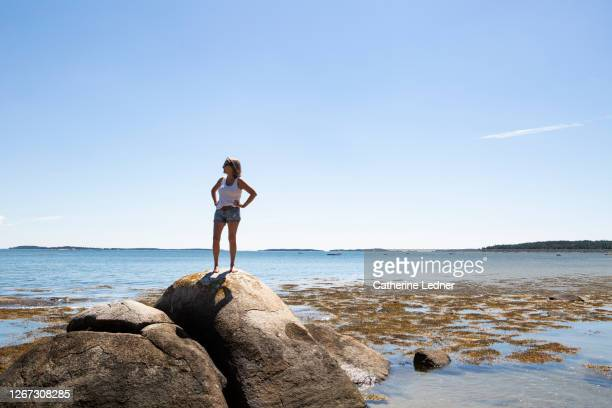 60's woman standing proudly on large rock on the maine coast - catherine ledner stock pictures, royalty-free photos & images