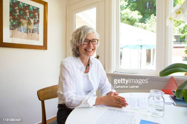 50's woman with grey hair smiling brightly at camera while seated at white table
