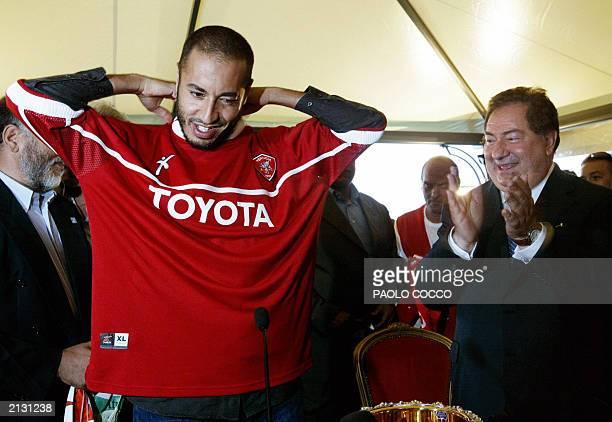 Saadi Kadhafi son of Libyan leader Moamar Kadhafi tries on his new Perugia soccer team jersey as the Italian team's president Luciano Gaucci applauds...