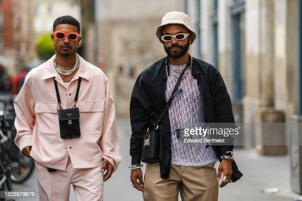Saam Nas wears neon orange sunglasses, silver earrings, silver chain and pearls necklaces, white ribbed tank-top, a pale pink oversized shirt with...