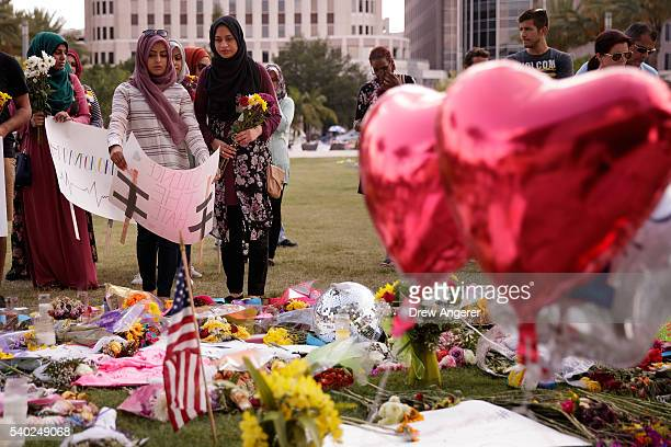 Saamiya Pirbhai and Atiya Karim from Husseini Islamic Center in Sanford Florida prepare to lay flowers and signs at a makeshift memorial at the Dr...