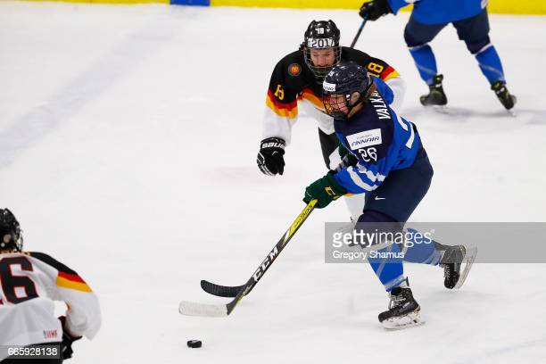 Saana Valkama of Finland skates past Bernadette Karpf of Germany during the second period in the bronze medal game at the 2017 IIHF Woman's World...