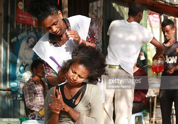 Saba Kiros a street barber who earns about 5 dollars from her daily work shapes her customer's hair on the roadside in Addis Ababa capital city of...
