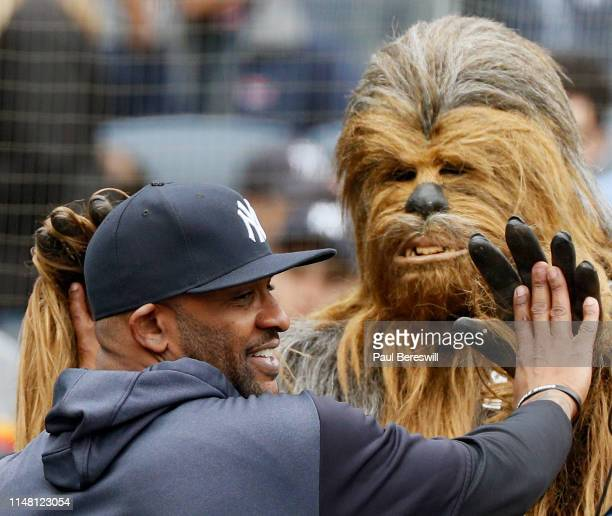 Sabathia of the New York Yankees greets the Star Wars character Chewbacca as characters from the movie paraded on the field before the first inning...
