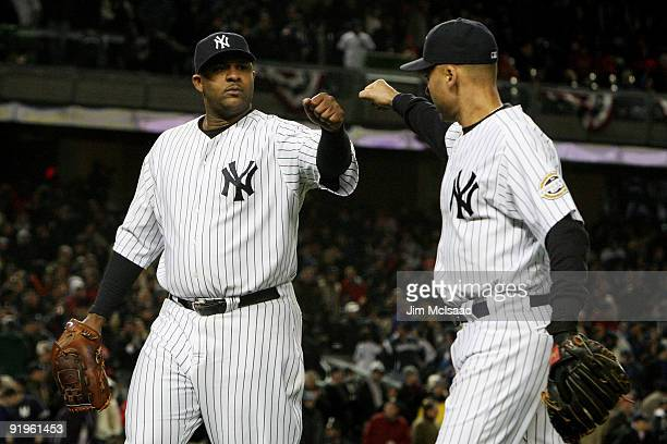 Sabathia of the New York Yankees walks off the field in the eighth inning and is congratulated by Derek Jeter during Game One of the ALCS against the...