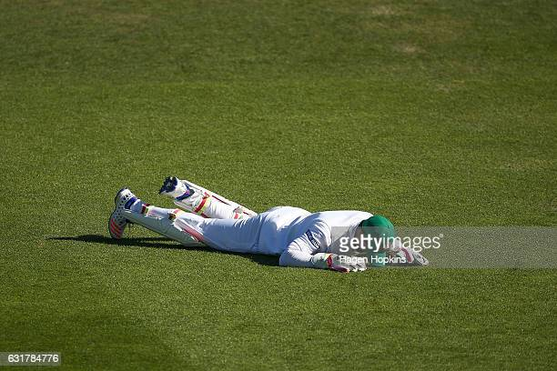 Sabbir Rahman of Bangladesh lies on the ground after a missed fielding opportunity during day five of the First Test match between New Zealand and...