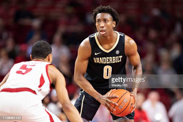 Saben Lee of the Vanderbilt Commodores looks to make a pass while being guarded by Jalen Harris of the Arkansas Razorbacks at Bud Walton Arena on...