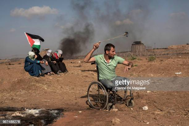 A legless Palestinian hurls a rock with a sling during clashes with Israeli forces Israeli troops fired live rounds and tear gas at Palestinians...