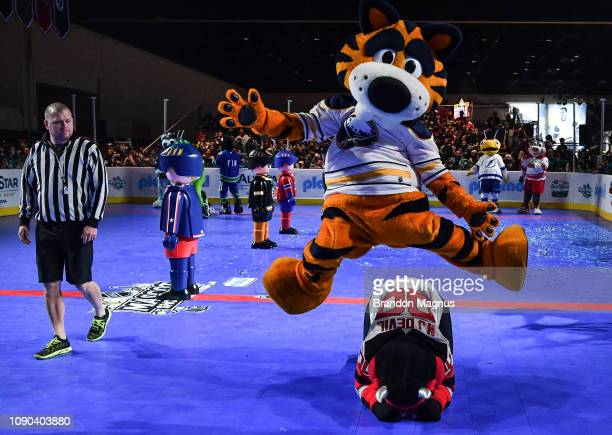 Sabertooth of the Buffalo Sabres jumps over NJ Devil of the New Jersey Devils during the NHL Mascot Showdown at San Jose McEnery Convention Center on...