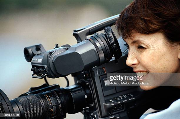 Sabine Azema looks through the camera on the set of the 1997 television movie Quand le Chat Sourit This is the French actress's directorial debut