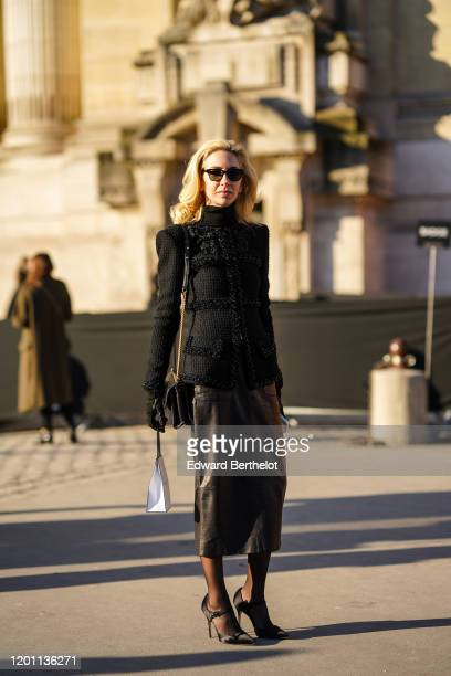 Sabine Getty wears sunglasses a black jacket with floral embroidery a black leather skirt tights high heel shoes outside Chanel during Paris Fashion...