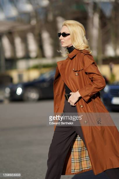 Sabine Getty wears sunglasses a brown trench coat with checkered inner lining from Burberry a black wool pullover a belt brown pants outside Burberry...
