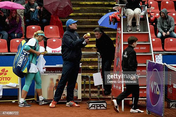 Sabine Lisicki of Germany leaves the court as play is suspended due to rain during her match against Lara Arruabarrena of Spain during Day Five of...