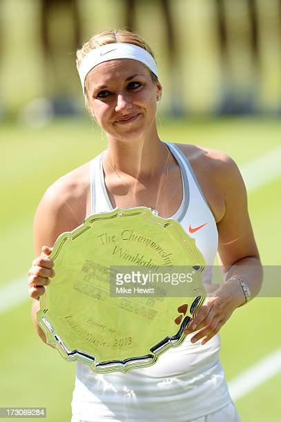 Sabine Lisicki of Germany poses with her runner-up trophy on Centre Court after her Ladies' Singles final match against Marion Bartoli of France on...