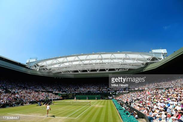Sabine Lisicki of Germany serves on Centre Court during the Ladies' Singles final match against Marion Bartoli of France on day twelve of the...
