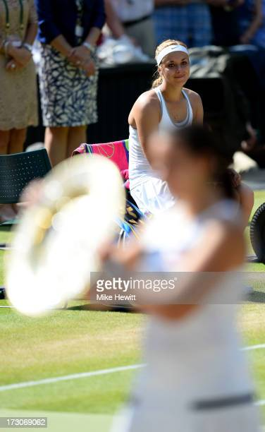 Sabine Lisicki of Germany watches as Marion Bartoli of France poses with the Venus Rosewater Dish trophy after their Ladies' Singles final match on...