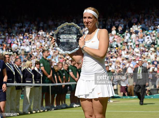 Sabine Lisicki poses with the runner-up trophy after being beaten by Marion Bartoli in the Ladies Singles Final on Day 12 of the Wimbledon Lawn...
