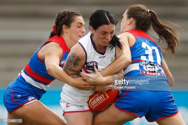 Sabreena Duffy of the Dockers is tackled by Elisabeth Georgostathis of the Bulldogs and Katy Herron of the Bulldogs during the round six AFLW match...