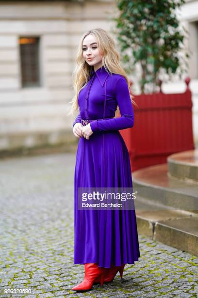 Sabrina Carpenter wears a purple dress and red boots and attends the Nina Ricci show as part of the Paris Fashion Week Womenswear Fall/Winter...