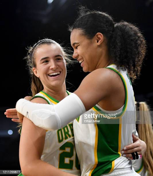 Sabrina Ionescu and Satou Sabally of the Oregon Ducks hug as they come out of the game late in their 89-56 victory over the Stanford Cardinal during...