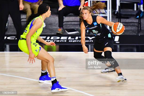 Sabrina Ionescu of the New York Liberty looks for a path around Isabelle Harrison of the Dallas Wings during the second half of a game at Feld...