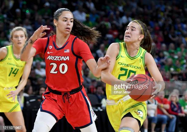 Sabrina Ionescu of the Oregon Ducks drives to the basket against Dominique McBryde of the Arizona Wildcats during the Pac-12 Conference women's...