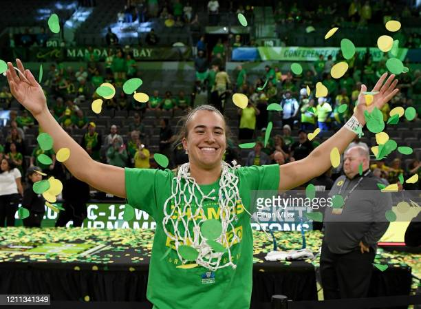 Sabrina Ionescu of the Oregon Ducks wears a basketball net around her neck and throws confetti in the air as she celebrates her team's 89-56 win over...