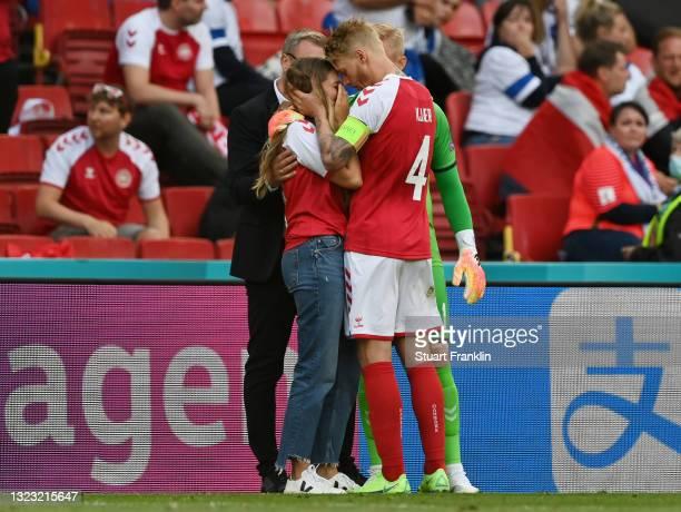 Sabrina Kvist Jensen, Girlfriend of Christian Eriksen of Denmark looks dejected as she is consoled by Simon Kjaer of Denmark whilst Christian Eriksen...