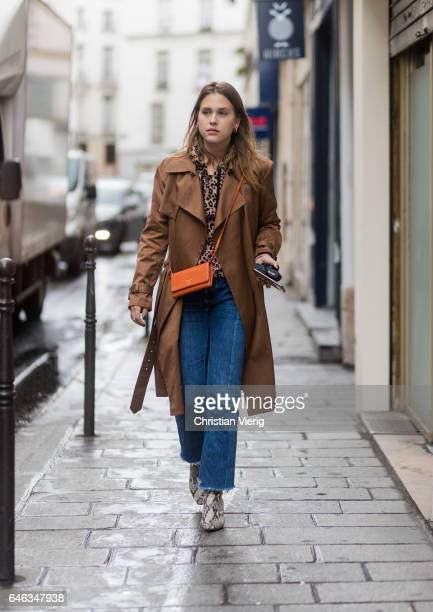 Sabrina Meijer wearing a brown trench coat orange Prada bag denim jeans outside AALTO on February 28 2017 in Paris France