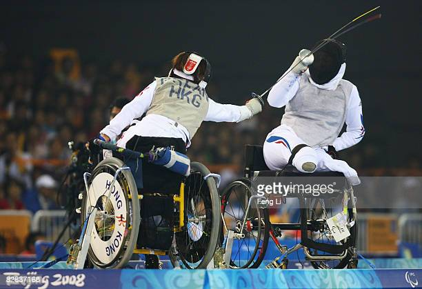 Sabrina Poignet of France and Fan Puishan of Hong Kong compete in the bronze medal match of the Women's Individual Foil Category A at Fencing Hall of...