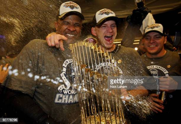 CC Sabthia AJ Burnett and Eric Hinske of the New York Yankees celebrate with the trophy in the locker room after their 73 win against the...