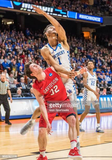 Sacha KilleyaJones of the Kentucky Wildcats and G Rusty Reigel of the Davidson Wildcats get tangled up under the basket during the NCAA Division I...