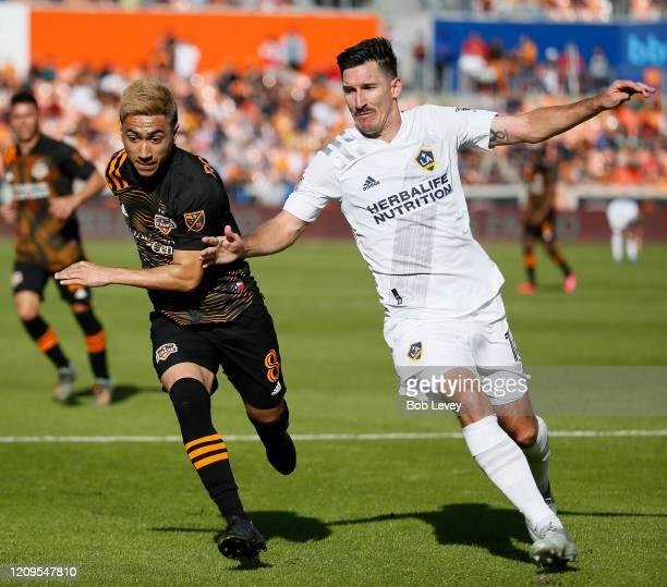 Sacha Kljestan of Los Angeles Galaxy races to get the ball before Memo Rodriguez of Houston Dynamo at BBVA Stadium on February 29 2020 in Houston...