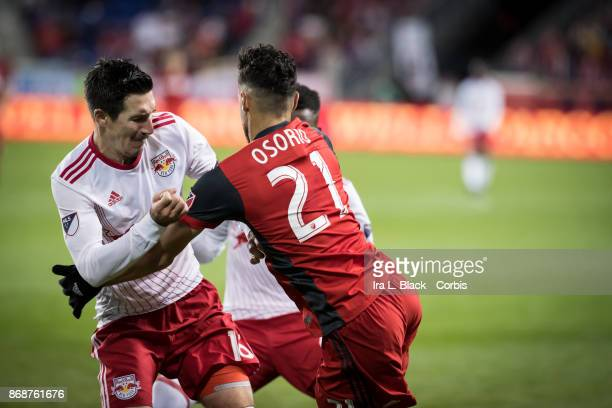 Sacha Kljestan of New York Red Bulls tries to muscle past Jonathan Osorio of Toronto FC during the Audi MLS Cup Playoff match between New York Red...